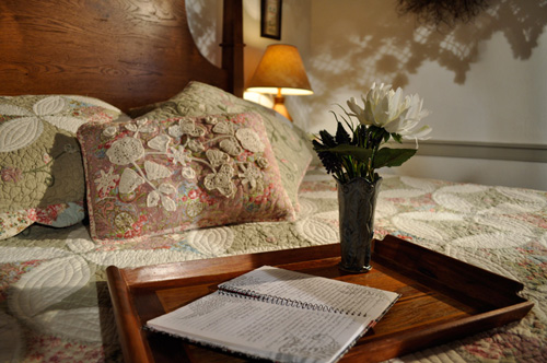 Needlework and quilted pillows adorn bed at the historic Jean Bonnet Tavern, Bedford, PA