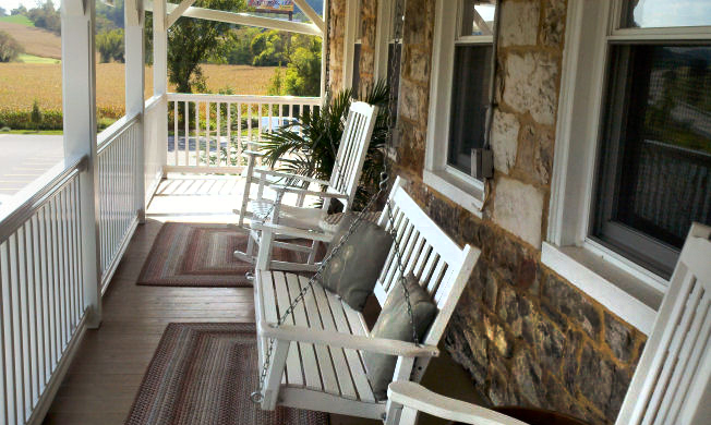 Comfy porch with swing and rocking chairs on upper balcony at the Jean Bonnet Tavern B&B